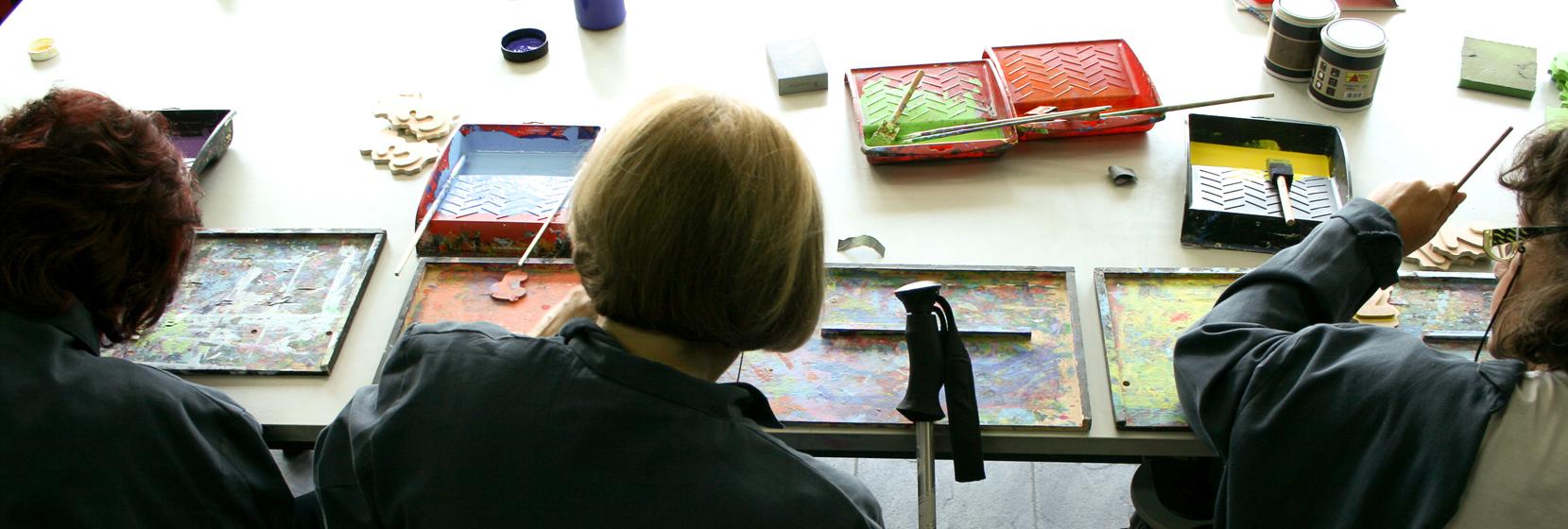 foto de tres mujeres de espaldas tranbajando en el taller de manual