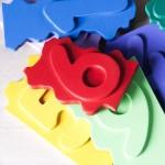 """Detalle del puzle """"1,2,3"""". [Descripción de imagen] Varias piezas-números esparcidas de forma desordenada sobre la base del puzle."""