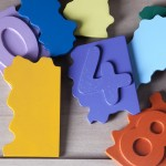 """Detalle del puzle """"1,2,3"""". [Descripción de imagen] Varias piezas de diferente color esparcidas de forma desordenada sobre la base del puzle."""