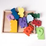 """Detalle del puzle """"1,2,3"""". [Descripción de imagen] Diez Piezas-números esparcidas de forma desordenada sobre la base puzle y fuera de ella."""