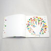 """Vista superior del libro """"Colores"""". [Descripción de imagen] Páginas interiores. A la derecha, pequeños trazos de pintura rodean la silueta de una mano. Bajo ésta, el texto: """"¡Uau! Tienes una mano mágica. ¿Seguimos?"""""""