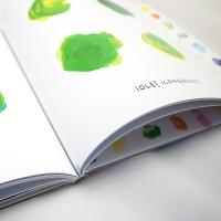 """Detalle del libro """"Colores"""". [Descripción de imagen] En páginas interiores, cuatro trazos con forma de puntos en color verde y el texto: """"¡Ole! ¡Conseguido!""""."""