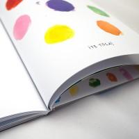 """Detalle del libro """"Colores"""". [Descripción de imagen] En páginas interiores, seis trazos con forma de punto en diferentes colores y el texto: """"Te toca""""."""