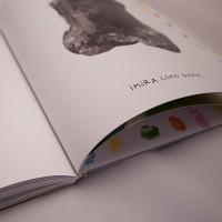 """Detalle del libro """"Colores"""". [Descripción de imagen] En páginas interiores, un trazo grueso oscuro con forma abstracta y el texto: """"Mira cómo queda""""."""