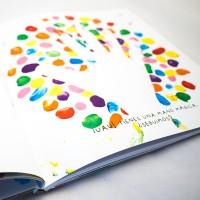 """Detalle del libro """"Colores"""". [Descripción de imagen] En páginas interiores, pequeños trazos de pintura rodean la silueta de una mano. Bajo ésta, el texto: """"¡Uau! Tienes una mano mágica. ¿Seguimos?"""""""