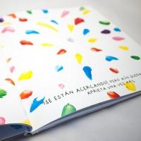 """Detalle del libro """"Colores"""". [Descripción de imagen] Páginas interiores. En ambas páginas, pequeños trazos de pintura de diferentes colores ocupan todo el espacio. En la parte inferior derecha, el texto: """"¡Se están acercando"""", pero aún queda. Aprieta una vez más."""""""