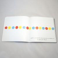 """Detalle del libro """"Colores"""". [Descripción de imagen] Páginas interiores. De izquierda a derecha, horizontalmente, círculos de diferente color. En la parte inferior, el texto: """"¡Umm! ¡Qué bonito! Pulsa los círculos amarillos, a ver qué pasa…""""."""