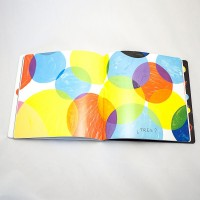 """Detalle del libro """"Colores"""". [Descripción de imagen] En ambas páginas, círculos de diferente tamaño y color ocupan todo el espacio. En la parte inferior, el texto: """"¿Tres?""""."""