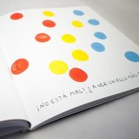 """Detalle del libro """"Colores"""". [Descripción de imagen] En páginas interiores, quince círculos de tres colores diferentes ocupando toda la hoja. En la parte inferior, el texto: """"¡No está mal!"""" ¿A ver un poco más?""""."""