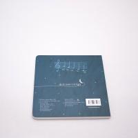 """Vista superior del libro """"Luna"""". [Descripción de imagen] En contraportada, el texto: """"De la cuna a la Luna"""". Sobre él, un pentagrama con notas. En la parte inferior, los créditos de autoría."""