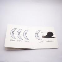 """Vista superior del libro """"Cocodrilo"""". [Descripción de imagen] Páginas interiores. A la izquierda, tres lunas y el texto: """"Luna, Luna, Luna"""". A la derecha, una luna, un caracol y el texto: """"Luna, Caracol""""."""