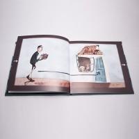 """Vista superior del libro """"El soldadito de plomo"""". [Descripción de imagen] Páginas interiores. De izquierda a derecha, una persona con un regalo en sus manos se dirige a una casa en la que asoma un niño por la ventana."""