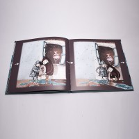 """Vista superior del libro """"El soldadito de plomo"""". [Descripción de imagen] Páginas interiores. A la izquierda, dos niños juegan bajo la lluvia con el soldadito. A la derecha, los niños introduciendo al soldadito en un barco de papel y un charco."""