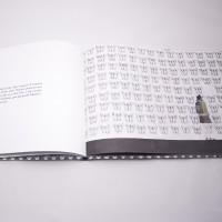 """Vista superior del libro """"Martín"""". [Descripción de imagen] Páginas interiores. A la izquierda, un fragmento de texto. A la derecha, la ilustración de una niña rodeada de mariposas ocupando todo el espacio."""