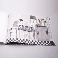 """Vista superior del libro """"Martín"""". [Descripción de imagen] En páginas interiores, Martín y su compañera están en una cocina observando una pecera con peces. En la barra, dos adultos cocinando."""