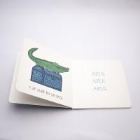 """Vista superior del libro """"Cocodrilo"""". [Descripción de imagen] Páginas interiores. A la izquierda, un cocodrilo y el texto: """"Y se sube en un baúl"""". A la derecha, el texto: """"Azul, azul, azul""""."""