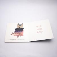 """Vista superior del libro """"Cocodrilo"""". [Descripción de imagen] Páginas interiores. A la izquierda, una granja con animales y el texto: """"Y la granja en un piojo"""". A la derecha, el texto: """"Rojo, rojo, rojo""""."""