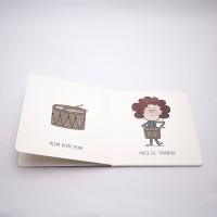 """Vista superior del libro """"Violín"""". [Descripción de imagen] A la izquierda, un tambor y el texto: """"Pom, pom, pom"""". A la derecha, una niña tocando el tambor y el texto: """"Hace el tambor""""."""