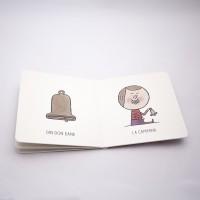 """Vista superior del libro """"Violín"""". [Descripción de imagen] A la izquierda, la ilustración de una campana y el texto: """"Din, don, dana"""". A la derecha, un bebé tocando la campana y el texto: """"La campana""""."""