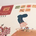 """Detalle del libro """"Nicolás cocina sin fuego"""". [Descripción de imagen] En páginas interiores, la ilustración de Nicolás preparando una brocheta de frutas. Sobre Nicolás, pictogramas de la receta."""