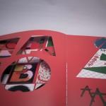 """Detalle del libro """"Hasta el infinito"""". [Descripción de imagen] Páginas interiores. Estilo modernista, A la izquierda, recortes en diferentes geométricas que dejan entrever la página anterior. A la derecha, figuras geométricas."""