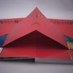 """Detalle del libro """"Hasta el infinito"""". [Descripción de imagen] Páginas interiores. En el centro de amas páginas, sobre un fondo de color rojo intenso, el dibujo de un rostro desplegable."""