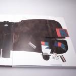 """Detalle del libro """"Hasta el infinito"""". [Descripción de imagen] Páginas interiores. Cubriendo ambas páginas, la ilustración de un gran hipopótamo. Sobre su superficie, ilustraciones de diferentes letras, formas y un rostro."""