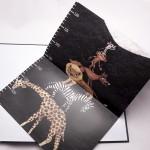 """Detalle del libro """"¿A qué sabe la luna?"""" [Descripción de imagen]. En el póster medidor que incluye, la ilustración de un ratón, un mono, un zorro, un león, una cebra y una jirafa, uno encima de otro. Unidad de medida: centímetros."""