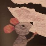 """Detalle del libro """"¿A qué sabe la luna?"""" [Descripción de imagen]. En él, la ilustración de un ratón mordiendo un trozo de luna."""