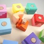 """Detalle del puzle """"Pasteles"""". [Descripción de imagen] Ocho piezas completas insertadas en los pivotes de la base del puzle. En el centro, dos semipiezas, una de ellas insertada."""
