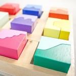 """Detalle del puzle """"Paisajes"""". [Descripción de imagen] Varias piezas completas de diferente color encajadas en la base del puzle."""