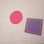 """Detalle del libro """"Por cuatro esquinitas de nada"""". [Descripción de imagen] En páginas interiores, dos recortes de telas en diferente tamaño y color sobre una tela de diferente tejido."""