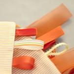 """Detalle del """"Conjunto sensorial"""" en tonos naranjas. Tiras de sujeción en varios estampados."""