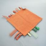 """Vista superior de la """"Mantita Dudú"""" en tonos naranjas y tejido de felpa."""