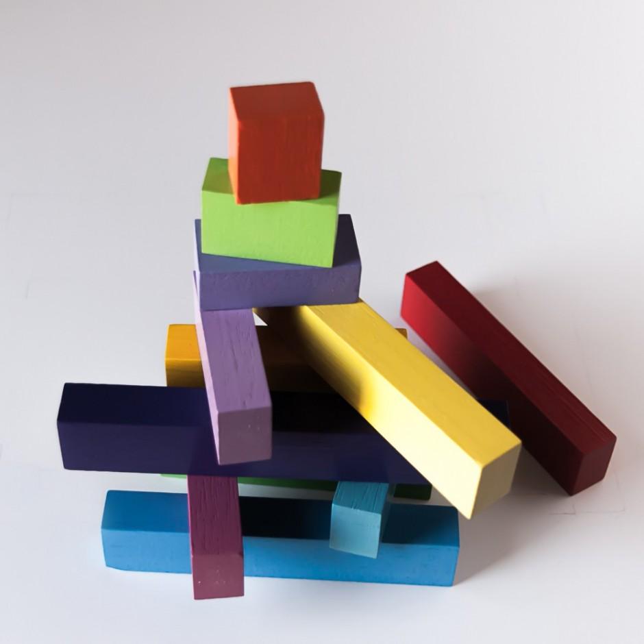 """Detalle del puzle """"La escalera"""". [Descripción de imagen] Varias piezas de diferente tamaño y color apiladas una sobre otra formando una montaña."""