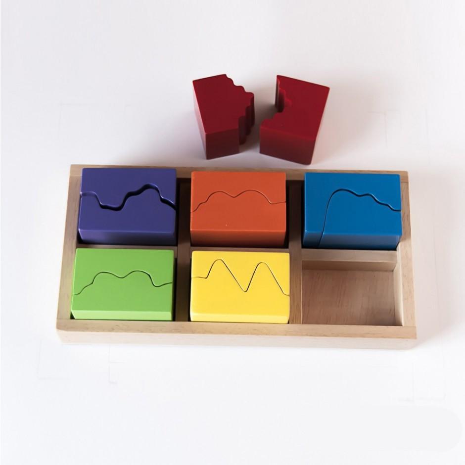 """Vista superior del puzle """"6x2"""". [Descripción de imagen] Cinco piezas completas encajadas en la base del puzle. Fuera de ésta, dos semipiezas."""