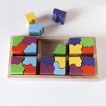 """Vista superior del puzle """"6x4"""". [Descripción de imagen] Cinco piezas completas encajadas en la base del puzle. Fuera de la base, tres semipiezas."""