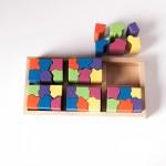 """Vista superior del puzle """"6x6"""". [Descripción de imagen] Cinco piezas completas encajadas en la base del puzle. Fuera de la base, seis semipiezas."""