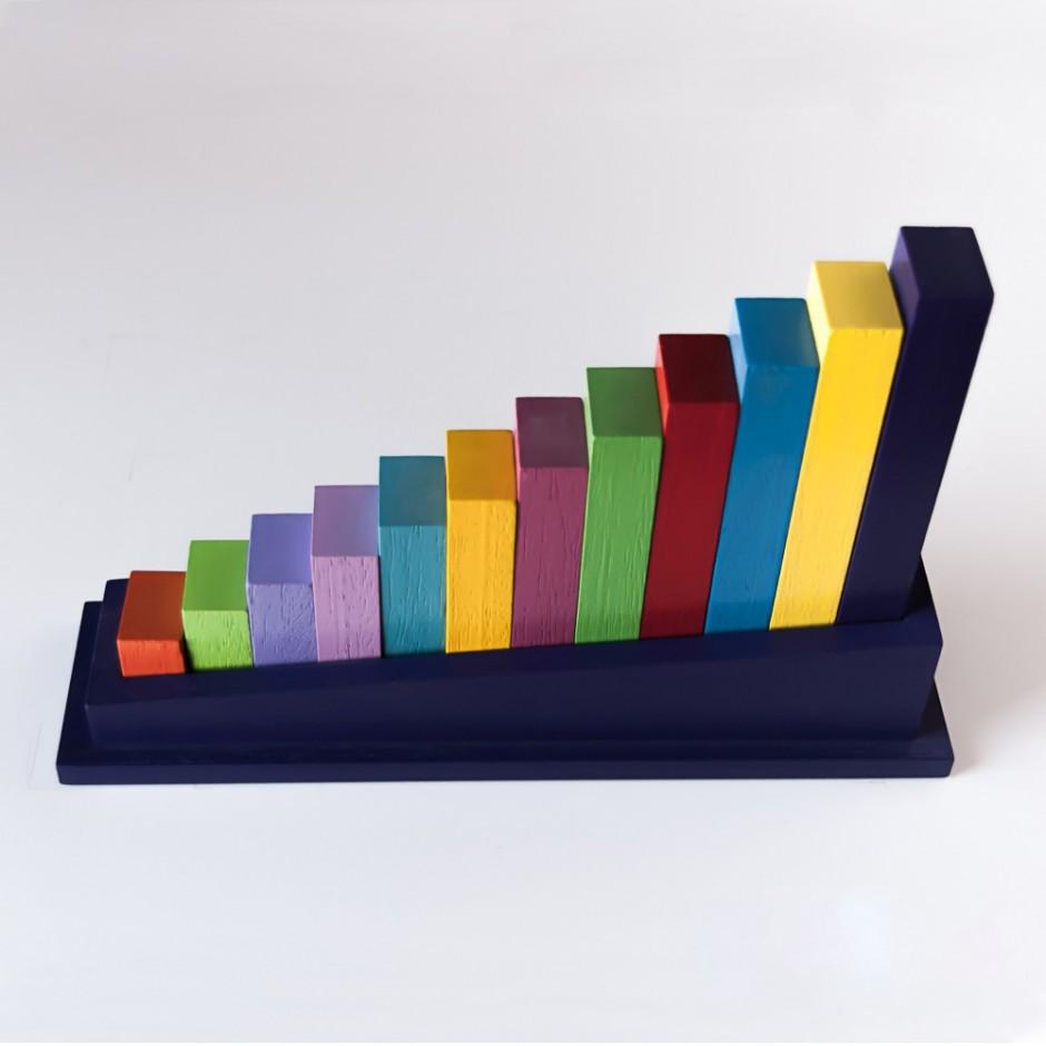 """Vista superior del puzle """"La escalera"""". [Descripción de imagen] Doce piezas de diferente color encajadas en la base del puzle. Ordenación según longitud."""