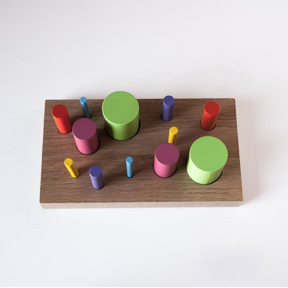 """Detalle de """"Juan y Pínchame"""". Doce piezas de diferente color encajadas en la base."""