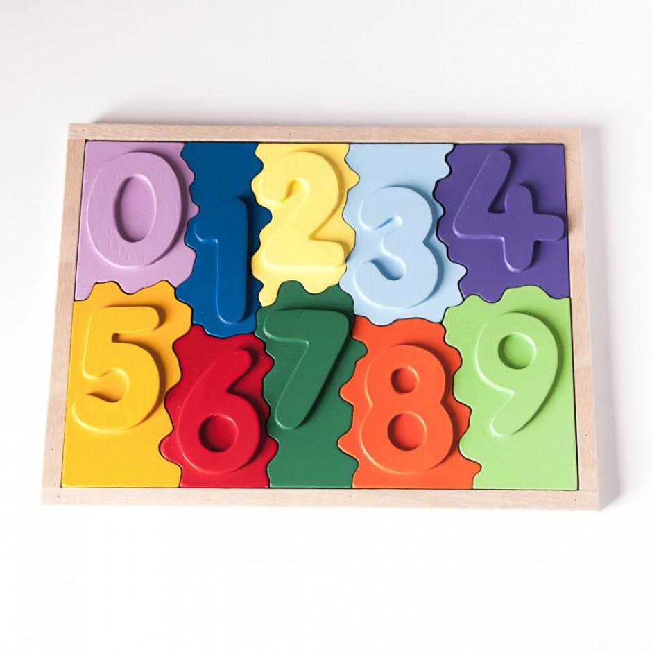 """Vista superior del puzle """"1,2,3"""". [Descripción de imagen] Piezas-números del 0 al 9 de diferente color encajadas en la base del puzle. Ordenación de menor a mayor."""
