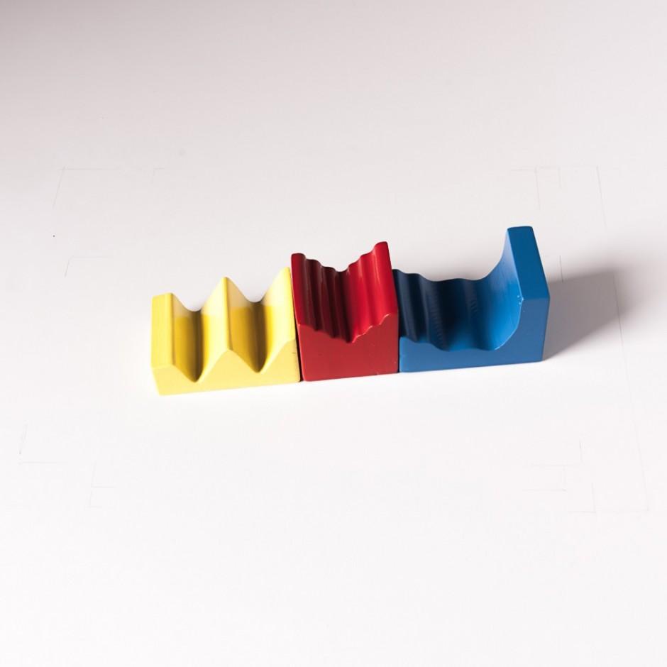 """Detalle del puzle """"6x2"""". [Descripción de imagen] Tres semipiezas de diferente forma y color dispuestas horizontalmente, una tras otra."""