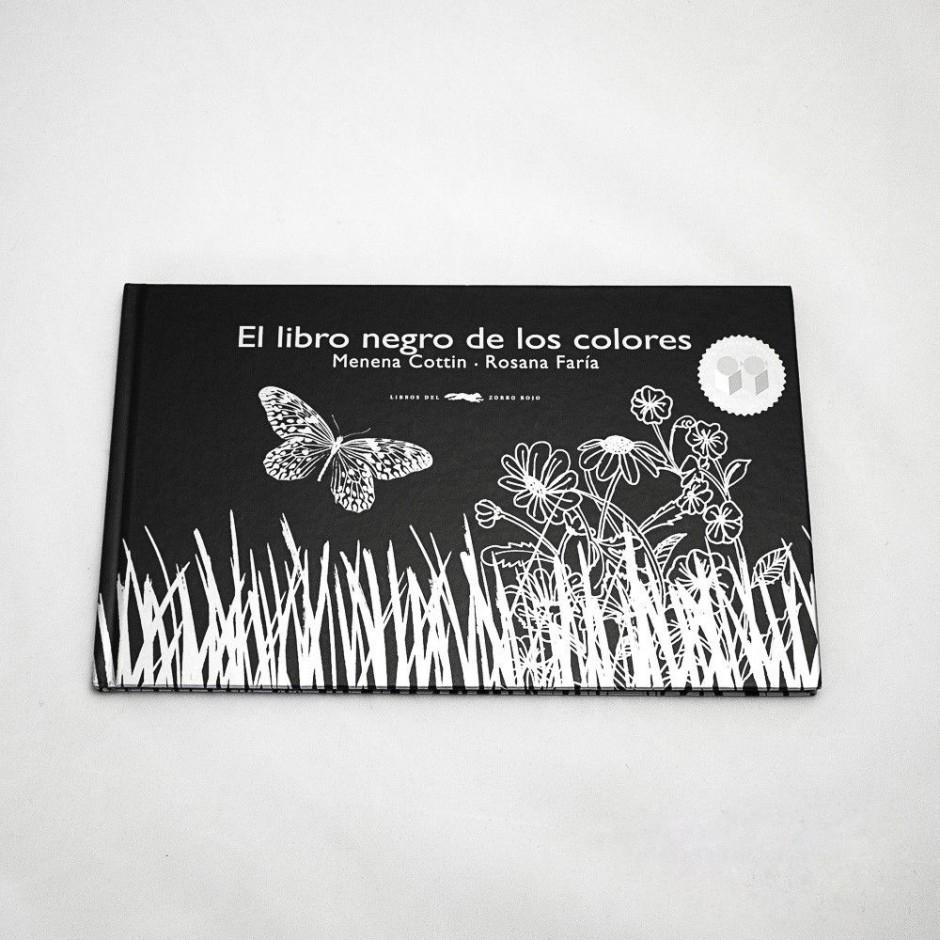 """Vista superior de """"El libro negro de los colores"""". [Descripción de imagen] En portada, la ilustración de una mariposa volando sobre hierba y flores."""