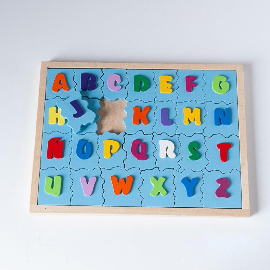 """Vista superior de """"A,B,C"""". Treinta y dos piezas (letras del abecedario latino) encajadas en la base."""