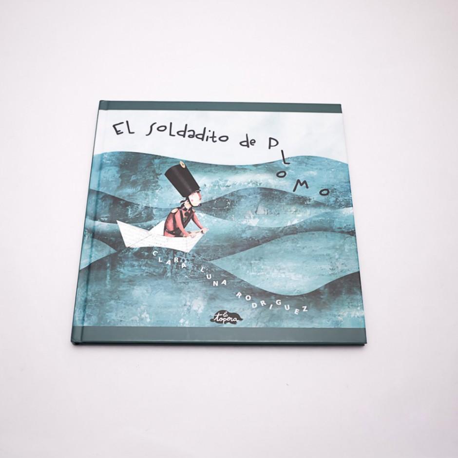 """Vista superior del libro """"El soldadito de plomo"""". [Descripción de imagen] En portada, la ilustración de un soldado en un barco de papel surcando el mar."""