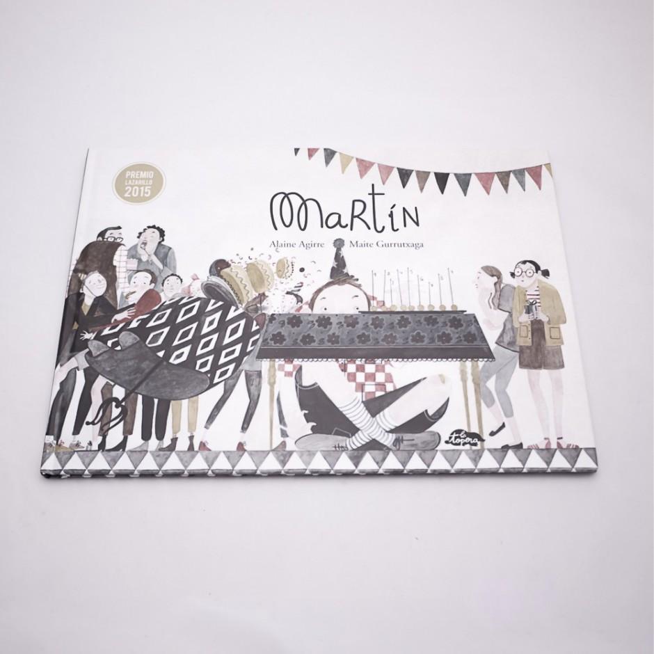 """Vista superior del libro """"Martín"""". [Descripción de imagen] En portada, la ilustración de varias personas en una fiesta, observando cómo alguien tropieza con una tarta, y un niño escondido tras una mesa."""