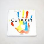 """Vista superior del libro """"Colores"""". [Descripción de imagen] En portada, la huella de la palma abierta de una mano en diferentes colores. En el centro, el título."""