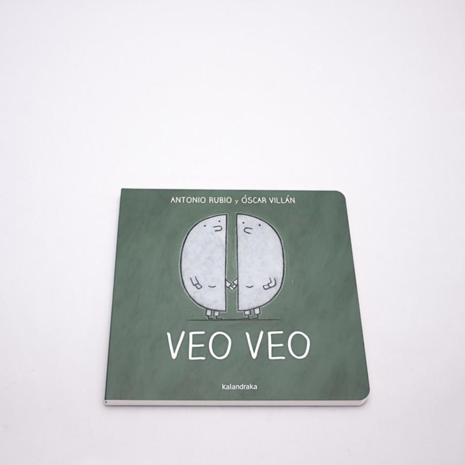 """Vista superior del libro """"Veo Veo"""".  En portada, la ilustración de dos lunas en cuarto creciente y menguante."""