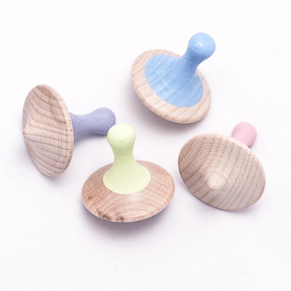 Vista superior de cuatro peonzas de madera en diferentes colores y posiciones.