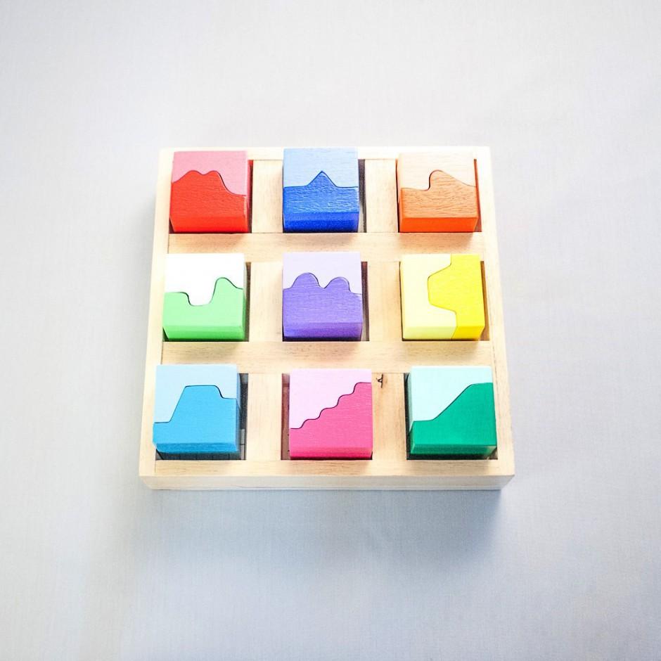 """Vista superior del puzle """"Paisajes"""". [Descripción de imagen] Nueve piezas completas en diferentes colores encajadas en la base del puzzle. Las piezas completas están formadas por dos semipiezas."""